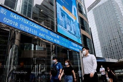 Gente con mascarilla en el distrito financiero de Hong Kong. La actividad económica, aún con muchas dificultades, se ha reactivado en buena parte del mundo, desde el peor momento de la pandemia.