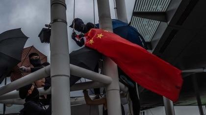 Manifestantes en Hong Kong bajan una bandera china que estaba izada en el distrito de Kowloon, el 3 de agosto. Credit Lam Yik Fei para The New York Times