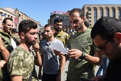 La gente asiste a una reunión para reclutar voluntarios militares después de que las autoridades armenias declararon la ley marcial y movilizaron a su población masculina después de los enfrentamientos con Azerbaiyán en la región dividida de Nagorno-Karabaj en Ereván, Armenia, el 27 de septiembre de 2020 (Reuters)