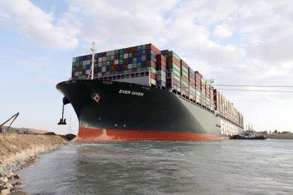 Una fotografía entregada por la Autoridad del Canal de Suez muestra un remolcador cerca del buque portacontenedores Ever Given que encalló en el Canal de Suez, Egipto. El Ever Given, un gran buque portacontenedores encalló en el Canal de Suez el 23 de marzo, bloqueando el paso de otros buques y causando un atasco de tráfico para los buques de carga. EFE/EPA/AUTORIDAD DEL CANAL DE SUEZ