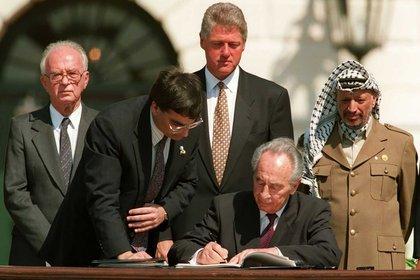 Momento histórico: Ante la mirada de Bill Clinton y Yasser Arafat, Shimon Peres firma el acuerdo de paz (AFP)