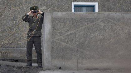 Un soldado norcoreano usa sus binoculares en las orillas del río Yalu cerca de Sinuiju, frente a la ciudad fronteriza china de Dandong el 14 de abril de 2017. (AFP/ Johannes EISELE)