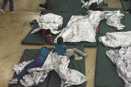 Niños detenidospor intentar entrar al país sin autorización descansan en una de las jaulas en el centro de McAllen, Texas, el domingo 17 de junio de 2018. (Oficina de Aduanas y Protección Fronterizavía AP)