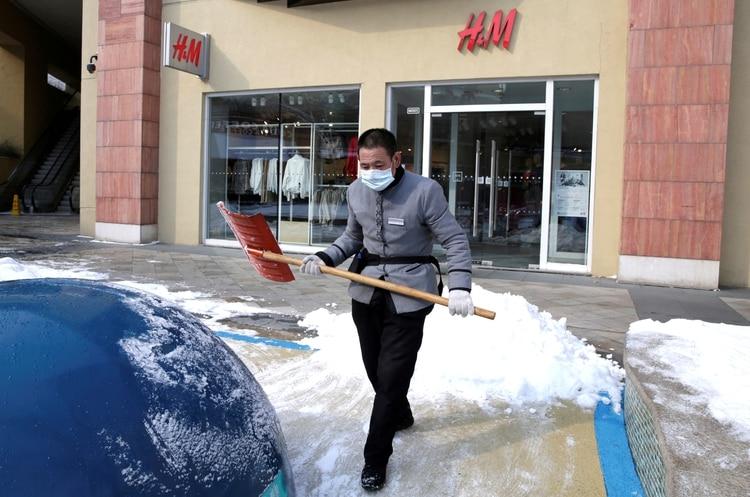 Un hombre limpia la vereda de un comercio en Beijing, China (REUTERS/Jason Lee/File Photo)