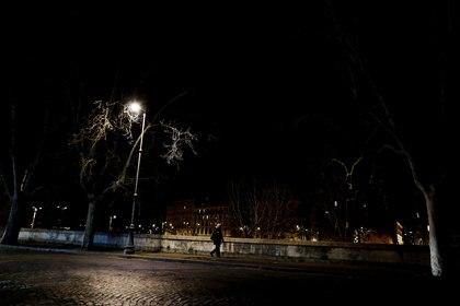 Una mujer camina por el río Tíber, después de un decreto que ordena que toda Italia esté encerrada en una represión sin precedentes destinada a vencer al coronavirus, en Roma, Italia, el 10 de marzo de 2020. (REUTERS / Yara Nardi)