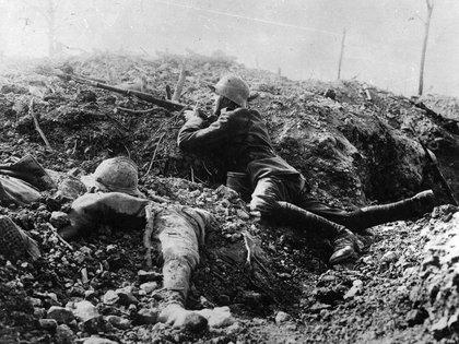 Un soldado alemán agazapado en los cráteres dejados por las bombas y junto al cadáver de un francés (Getty)