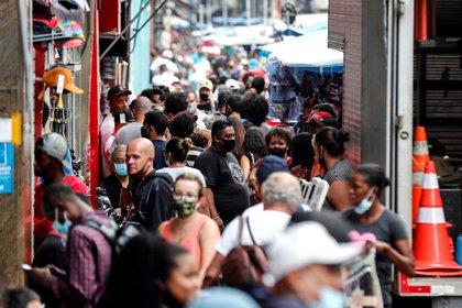 Decenas de personas caminan en una concurrida vía comercial en el centro de San Pablo (EFE/ Sebastiao Moreira/Archivo)