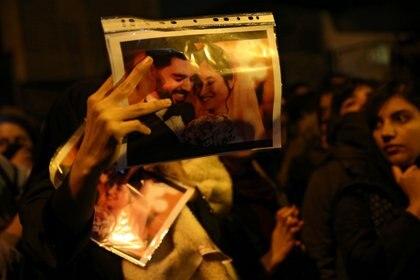 Una mujer muestra la foto de un matrimonio, víctima del derribo del avión ucraniano, durante las protestas en Teherán contra el régimen (Reuters)