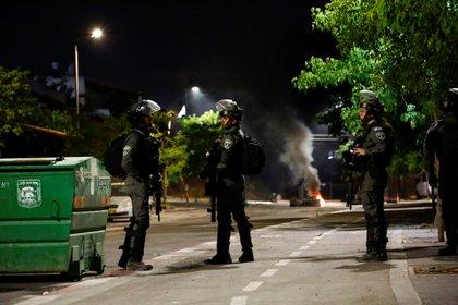 Miembros de la policía fronteriza israelí permanecen cerca de neumáticos quemados luego de disturbios violentos en la ciudad árabe-judía de Lod este jueves (REUTERS/Corinna Kern)
