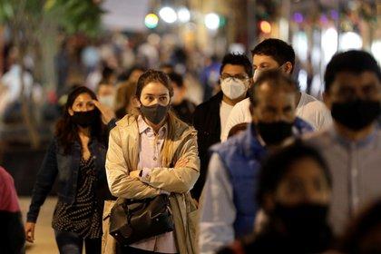 Una mujer con una mascarilla protectora hace cola para cruzar una calle, mientras continúa el brote de la enfermedad por coronavirus (Foto: EFE)