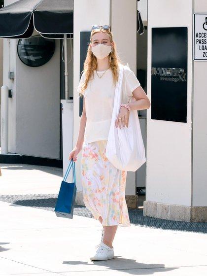 Elle Fanning salió de compras con su madre en Los Ángeles. Protegida con tapaboca, la actriz de 22 años lució una remera blanca, una pollera con estampado floral y zapatillas deportivas blancas. Además llevó un gran bolso de mano (Foto:  The Image Direct / The Grosby Group)