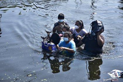 Una familia camina hoy por entre una calle inundada en Villahermosa, en el estado de Tabasco (México). EFE/Jaime Ávalos