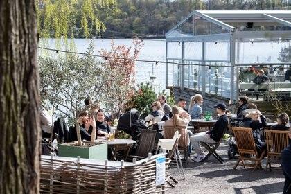 Personas disfutando los primeros días de primavera en un restaurante durante la pademia en Estocolmo (Jessica Gow/TT News Agency/REUTERS)