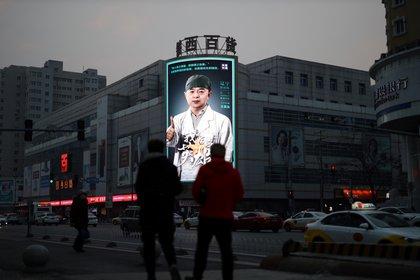 Personas observan en la pantalla un homenaje a los médicos enviados a Wuhan para luchar contra el coronavirus (STR/ AFP)