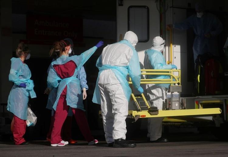 Personal médico con ropa de protección saca a un paciente de una ambulancia en el hospital de St Thomas, mientras continúa la propagación del coronavirus, en Londres, Reino Unido, 31 de marzo de 2020. REUTERS/Hannah McKay