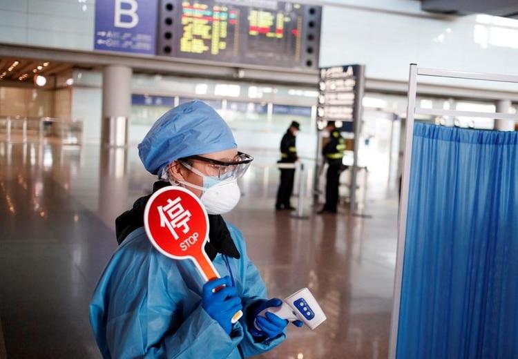 Foto del miércoles de un empleado con ropas de protección preparado para tomar la temperatura de los visitantes en el aeropuerto de Pekín. Mar 4, 2020. REUTERS/Thomas Peter