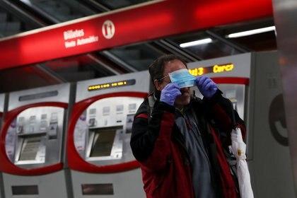 Un pasajero se coloca una mascarilla repartida en el metro de Madrid (Reuters)