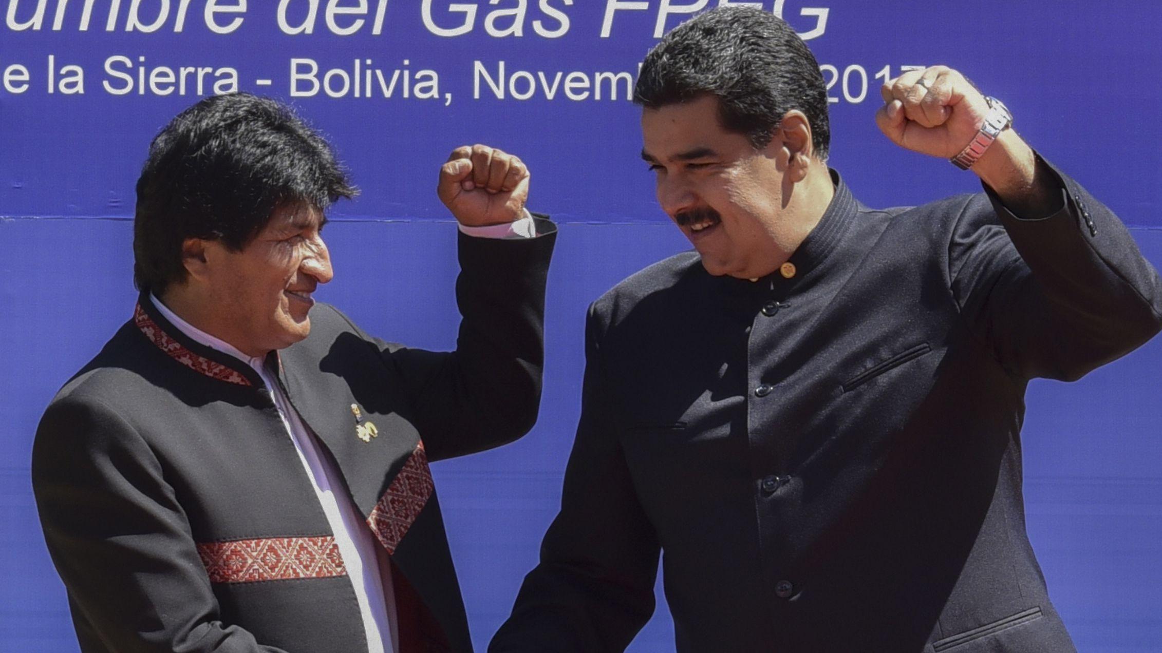 Maduro y Morales levantan el puño izquierdo en una cumbre en Santa Cruz de la Sierra en 2017 (Photo by Aizar RALDES / AFP)