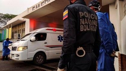 Trabajadores de la salud y miembros de la Policía Nacional Bolivariana observan la llegada de una ambulancia con prisioneros fuera de un hospital en Guanare, Venezuela (REUTERS/Manuel Alvarado)