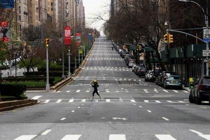 Una mujer cruza el vacío de la calle Park Avenue en Manhattan mientras el brote de la enfermedad por coronavirus (COVID-19) continúa en Nueva York, EEUU [5 de abril de 2020] (Reuters/ Eduardo Munoz)