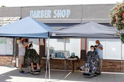 Peluqueros atienden clientes de acuerdo con su protocolo en Solana Beach, California. REUTERS/Mike Blake