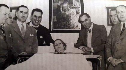 Eva Perón, ya muy enferma, rodeada por Juan Domingo Perón, y los doctores Raúl Mendé, Armando Mendez San Martín, Roberto Goyenechea, Ricardo Finocchieto, Jorge Albertelli y Raúl Apold. (Foto: Cien días de Eva Perón)