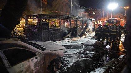Bomberos israelíes apagan vehículos dañados en la ciudad de Holon cerca de Tel Aviv. (Photo by ahmad gharabli / AFP)