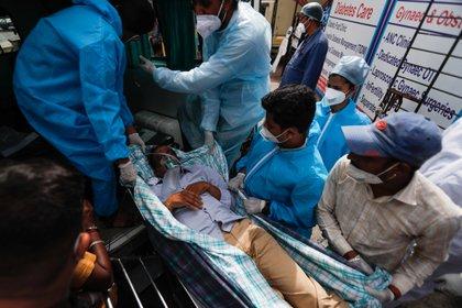 Un paciente con COVID-19 es evacuado de un hospital después de que se incendiara en Virar, en las afueras de Mumbai (Reuters)