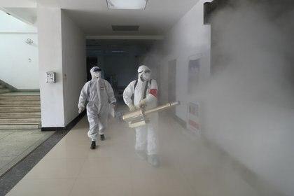 Imagen de archivo de voluntarios con trajes de protección desinfectan un edificio residencial en Wuhan, China, Febrero 22, 2020. China Daily vía REUTERS
