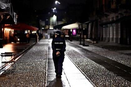 Un oficial de policía vigila una calle, mientras la región de Lombardía impone un toque de queda después de haber sido golpeada por una oleada de infecciones de la enfermedad coronavirus (COVID-19), en Milán, Italia, el 22 de octubre de 2020. REUTERS/Flavio Lo Scalzo