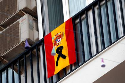 A Spanish flag with a black ribbon hangs from a balcony, amid the coronavirus disease (COVID-19) outbreak, in downtown Ronda, southern Spain, April 7, 2020. REUTERS/Jon Nazca