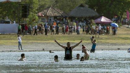 Personas asisten al balneario Laguna de Xiloa, en las afueras de Managua (Nicaragua). Miles de simpatizantes del partido oficialista Frente Sandinista de Liberación Nacional (FSLN) volvieron a retar la pandemia de COVID-19 el domingo pasado, con desplazamientos multitudinarios a balnearios y fiestas populares (EFE/Jorge Torres)