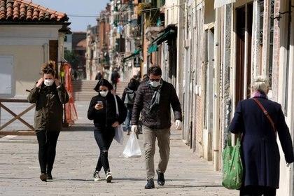 Ciudadanos usan máscaras protectoras en las calles de Venecia durante la actual emergencia por la enfermedad COVID-19, provocada por el coronavirus, en Venecia, Italia [25 de marzo de 2020] (Reuters/ Manuel Silvestri)