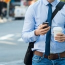 Businessman using smartphone and holding paper cup ina urban scene. Worried businessman in walking on the road and messaging with phone. Young man text messaging through cell phone while walking on the road in the city centre.