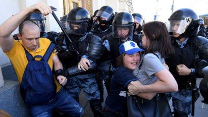 Un niño abraza a su madre y se protege del avance policial (Photo by Kirill KUDRYAVTSEV / AFP)