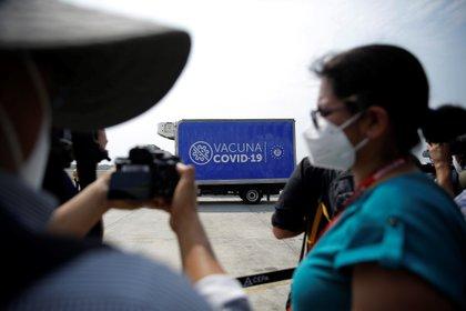 Un hombre toma fotografías a personal sanitario antes de recibir la vacuna contra la covid-19 en San Salvador. EFE/Rodrigo Sura