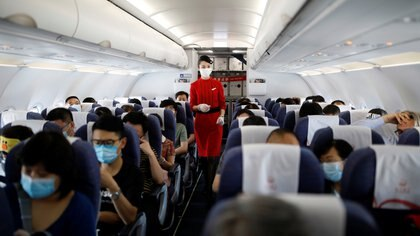 A flight attendant wearing a face mask and gloves following the coronavirus disease (COVID-19) outbreak walks past passengers inside a Sichuan Airlines aircraft before the flight takes off from Xichang Qingshan Airport in Xichang, Sichuan province, China June 16, 2020.  REUTERS/Carlos Garcia Rawlins