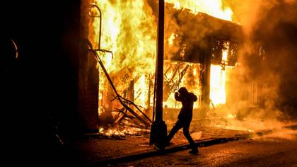 Un joven en medio del fuego en Minneapolis, Minnesota (Chandan KHANNA / AFP)