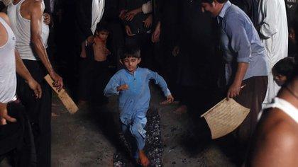 Otro niño es obligado a caminar en las brasas ante el aliento de los adultos (AFP)