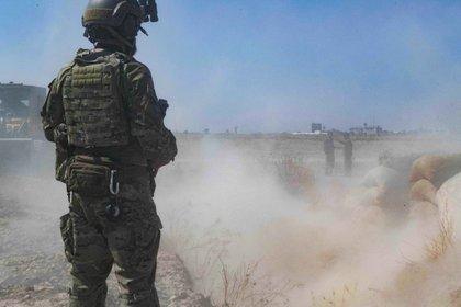 """En esta imagen del 21 de septiembre de 2019 proporcionada por el Ejército de Estados Unidos, un soldado estadounidense supervisa mientras miembros de las Fuerzas Democráticas Sirias derriban una fortificación de los combatientes kurdos dentro de la llamada """"zona segura"""" cerca de la frontera turca. (Ejército de Estados Unids, foto del sargento  Andrew Goedl via AP)"""