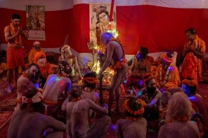 """Naga Sadhus, u hombres santos hindúes, esperan antes de la procesión para darse un chapuzón en el río Ganges durante Shahi Snan en """"Kumbh Mela"""", o el Festival del Lanzador, en medio de la propagación de la enfermedad del coronavirus, en Haridwar, India. , 12 de abril de 2021."""