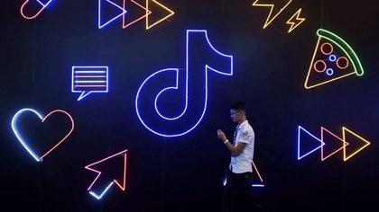 FOTO DE ARCHIVO: Un hombre con un teléfono pasa junto a un cartel de la aplicación TikTok de la compañía china ByteDance, conocida localmente como Douyin, en una Exposición Internacional en Hangzhou, provincia de Zhejiang, China. 18 de octubre de 2019. REUTERS/Colaborador. ATENCIÓN EDITORES -  ESTA IMAGEN HA SIDO ENTREGADA POR UN TERCERO.