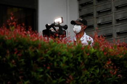 A video journalist wearing a protective mask uses a camera at Halim Perdanakusuma airport, following the outbreak of the coronavirus in China, in Jakarta, Indonesia, February 15, 2020. REUTERS/Willy Kurniawan