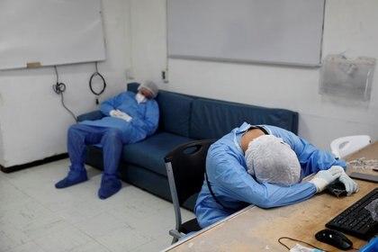 Trabajadores médicos con trajes protectores descansan después de horas de tratar a pacientes que padecen COVID-19, la enfermedad causada por el coronavirus, en una unidad de cuidados intensivos en el Hospital Juárez de México, en la capital del país. 29 de octubre de 2020. REUTERS / Carlos Jasso