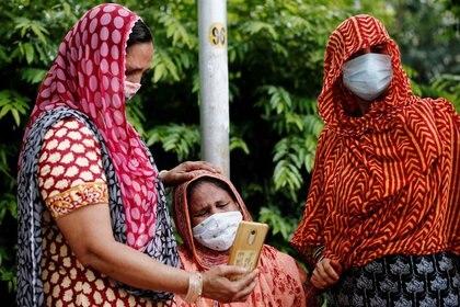 FOTO DE ARCHIVO: Una mujer, de luto, mientras mira una fotografía en un teléfono móvil del cuerpo de su marido, fallecido por COVID-19, a las afueras de un depósito de cadáveres en Nueva Delhi, India. 9 de julio de 2020. REUTERS/Adnan Abidi