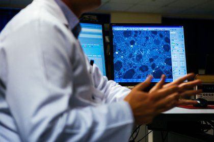 An employee uses a computer screen to show a magnified kimberlite rock sample to visitors during a presentation on carbon storage in a laboratory, operated by De Beers SA, in Johannesburg, South Africa, on Tuesday, May 3, 2017. The Anglo American Plc unit plans to store carbon-dioxide in kimberlite -- a type of ore best known for containing diamonds, but which also naturally reacts with carbon to remove it from the atmosphere. Photographer: Waldo Swiegers/Bloomberg