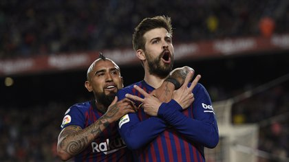 Barcelona's Spanish defender Gerard Pique (R) celebrates with Barcelona's Chilean midfielder Arturo Vidal after scoring a goal during the Spanish league football match between FC Barcelona and Rayo Vallecano de Madrid at the Camp Nou stadium in Barcelona on March 9, 2019. (Photo by LLUIS GENE / AFP)