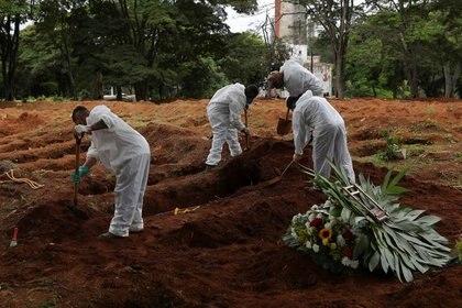 Foto de archivo de trabajadores de un cementerio en Sao Paulo depositando el ataúd de un fallecido como consecuencia del coronavirus.  Dic 25, 2020. REUTERS/Amanda Perobelli