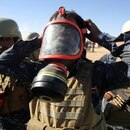 An Iraqi policeman tries on a gasmask at the Qayyarah military base, about 60 kilometres (35 miles) south of Mosul, on October 16, 2016, as they prepare for an offensive to retake Mosul, the last major population centre in the country, after regaining much of the territory the jihadists seized in 2014 and 2015. / AFP PHOTO / AHMAD AL-RUBAYE