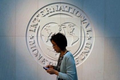 FOTO DE ARCHIVO. Una mujer pasa frente al logo del Fondo Monetario Internacional (FMI), en su sede en Washington DC, EEUU. Foto: REUTERS/Yuri Gripas